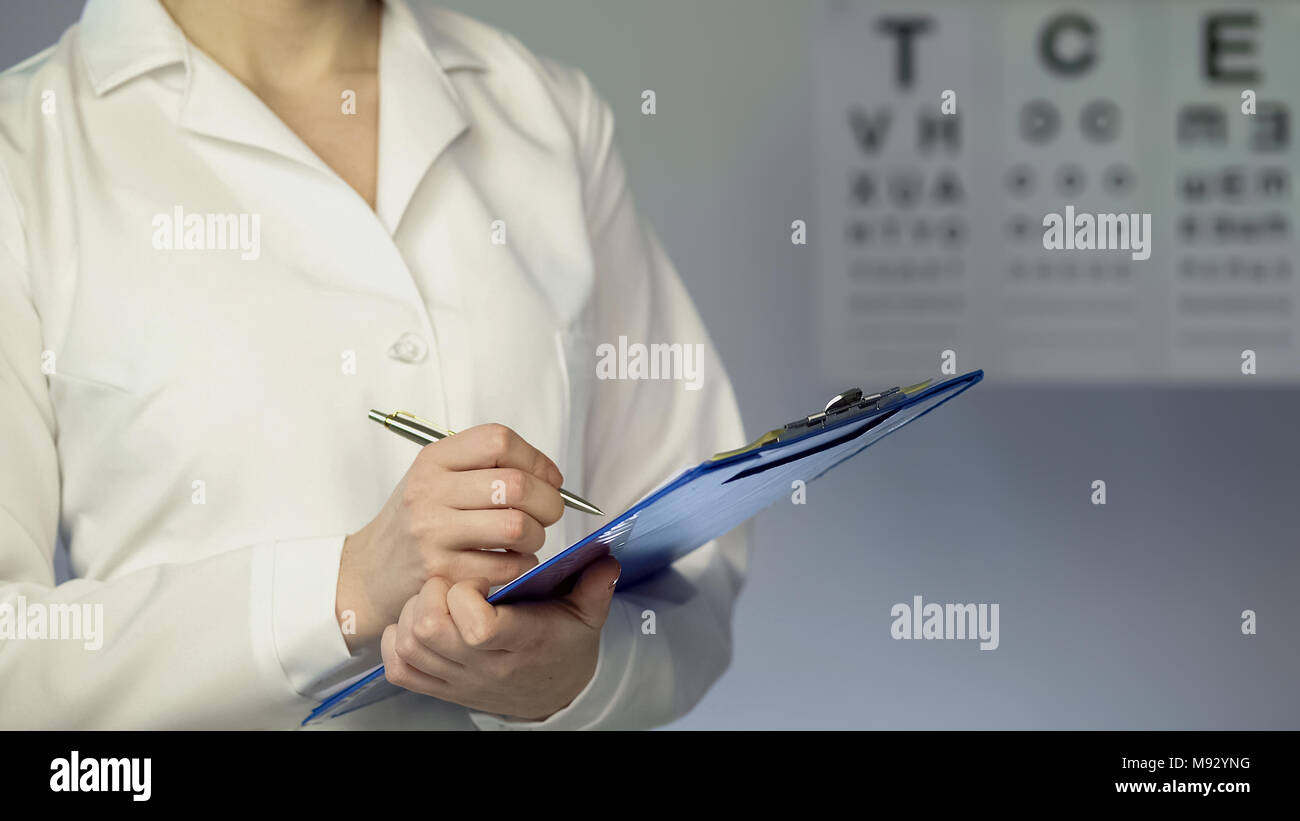 Female ophthalmologist writing down patient diagnosis and treatment, examination - Stock Image