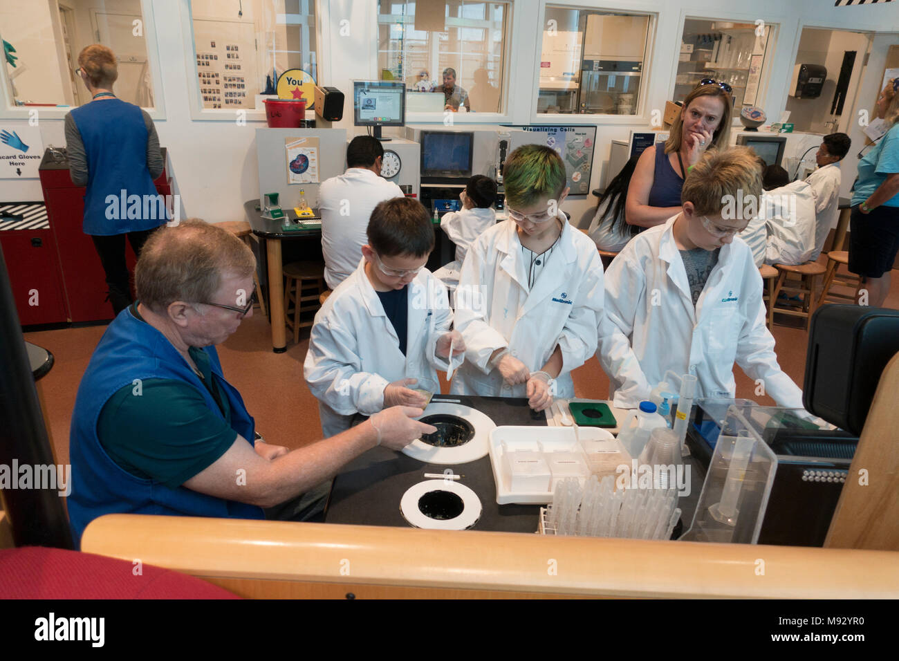 Instructor at Science Museum of MN laboratory working with white coated students age 10 perform experiments mom watching. St Paul Minnesota MN USA - Stock Image