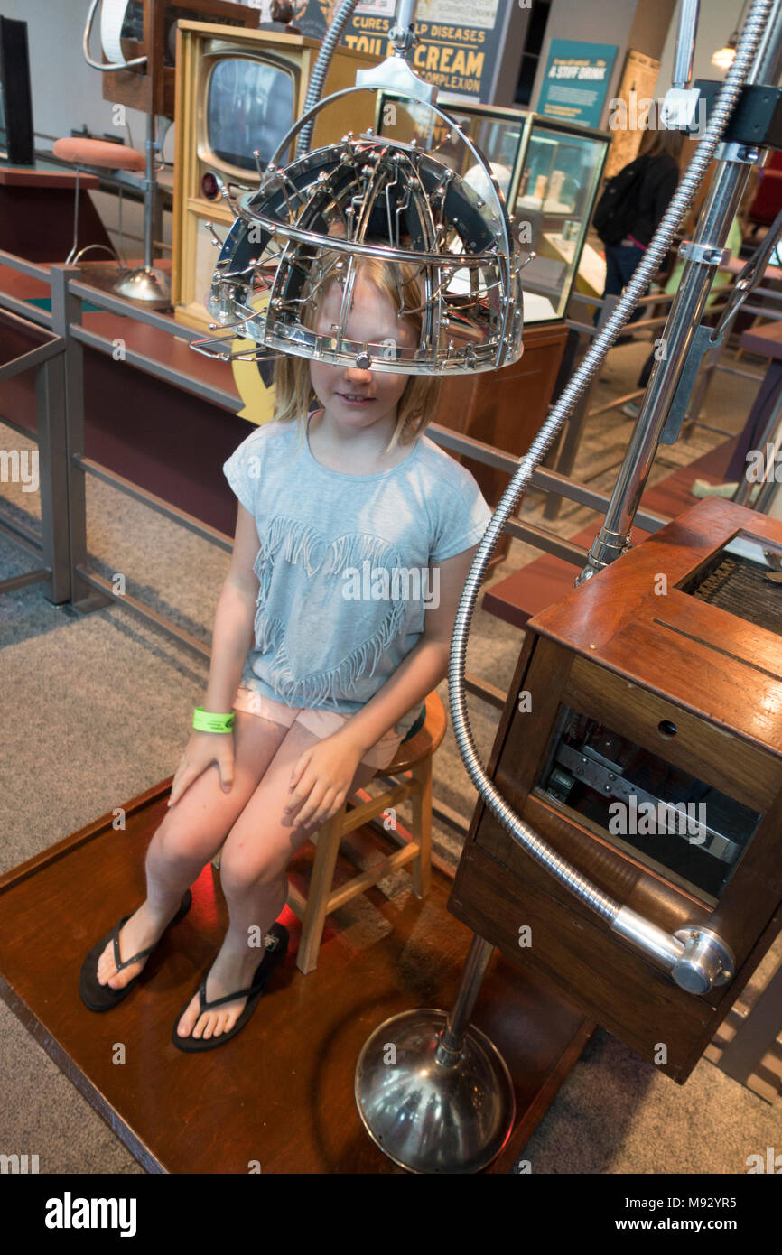 Girl age 10 sits under Psychograph early 20th century Phrenology Machine Measures the Shape of Your Head at Science Museum. St Paul Minnesota MN USA - Stock Image