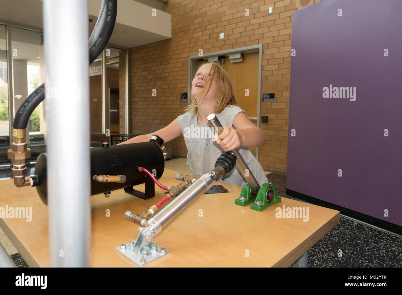 Young preteen girl pumping the Ping Pong Ball launcher with an air cannon Science Museum of Minnesota exhibit. Minneapolis Minnesota MN USA - Stock Image