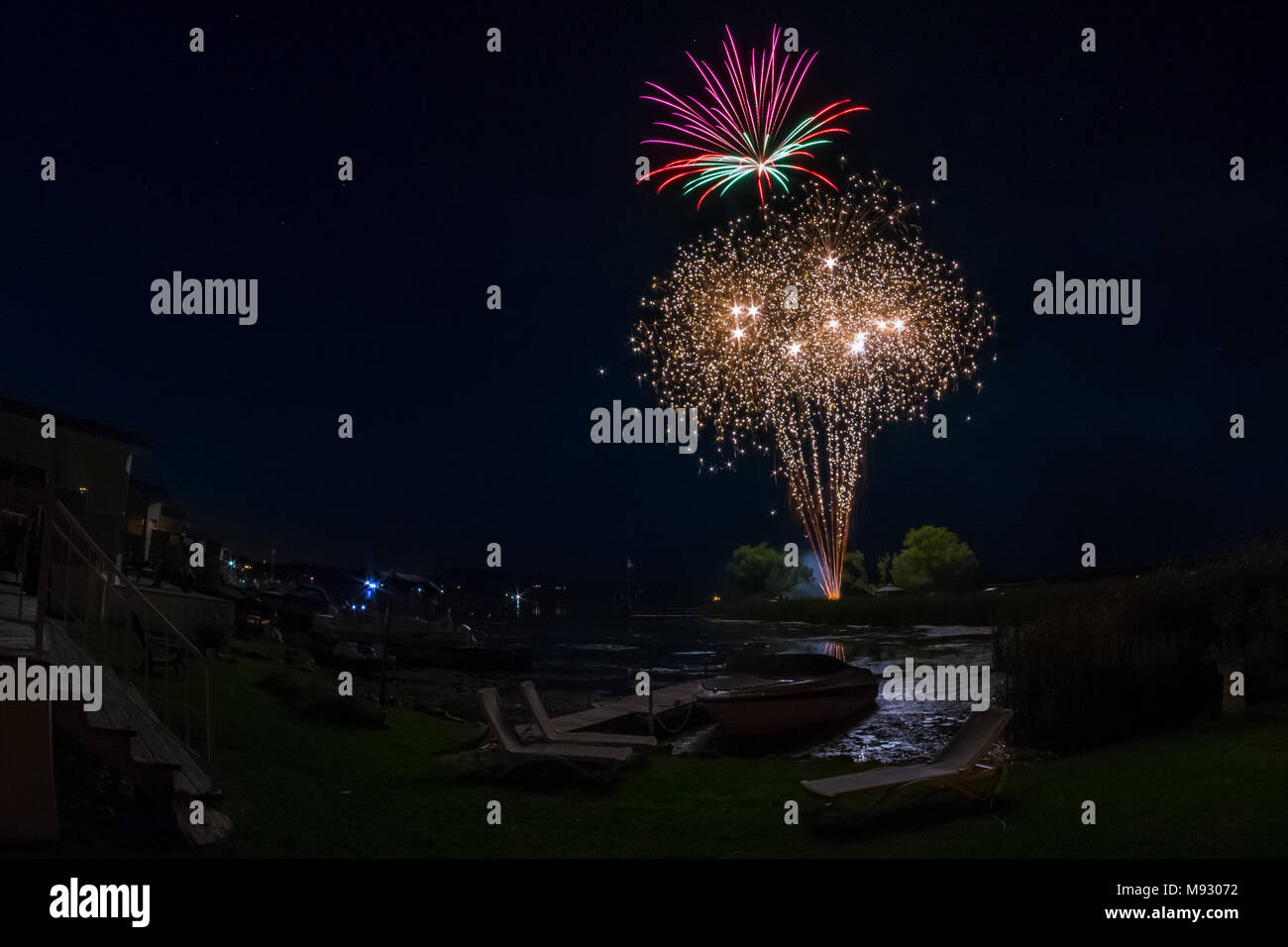 Fireworks over cottage lake showing cottages,boats and dock on the background - Stock Image