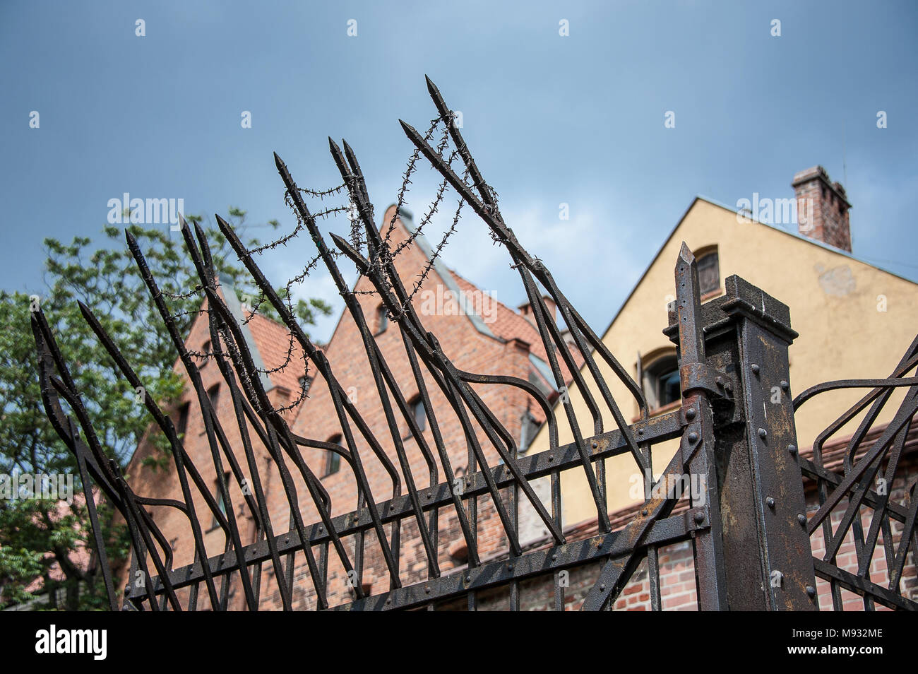 Security measures around a  detention centre complex in Torun, Poland. Barbed wire, high fence, jagged spikes  against blue sky background - Stock Image
