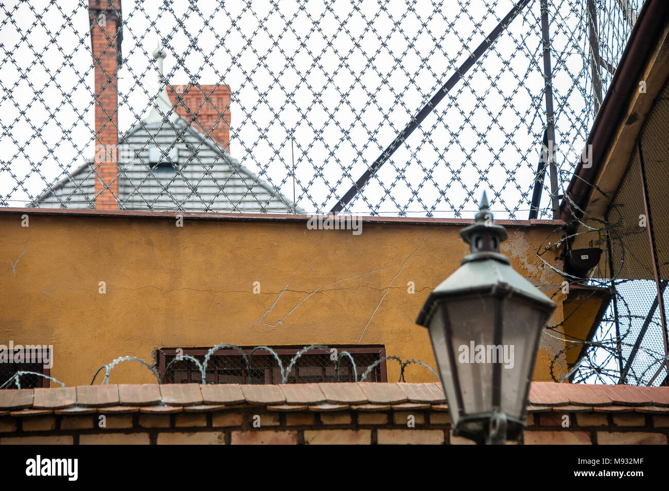 Security measures around a detention centre building in Torun, Poland. Razor wire, high wall, rooftop view - Stock Image