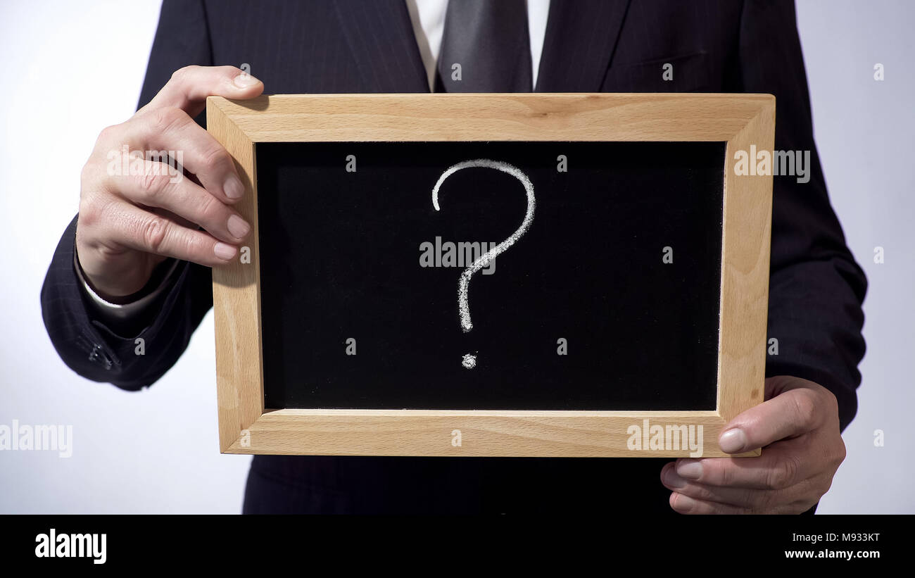 Question mark written on blackboard, business person holding a sign in hands Stock Photo