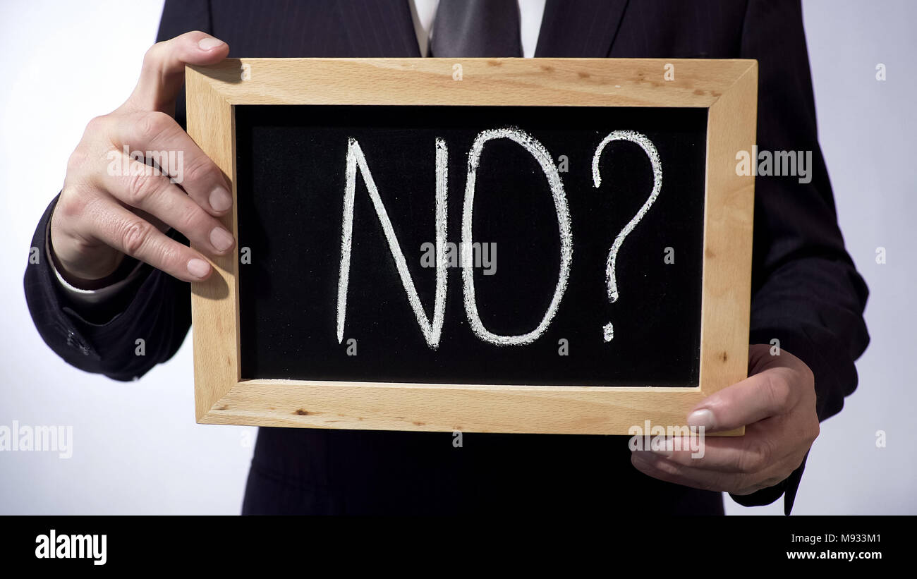No with question mark written on blackboard, businessman holding sign, concept Stock Photo
