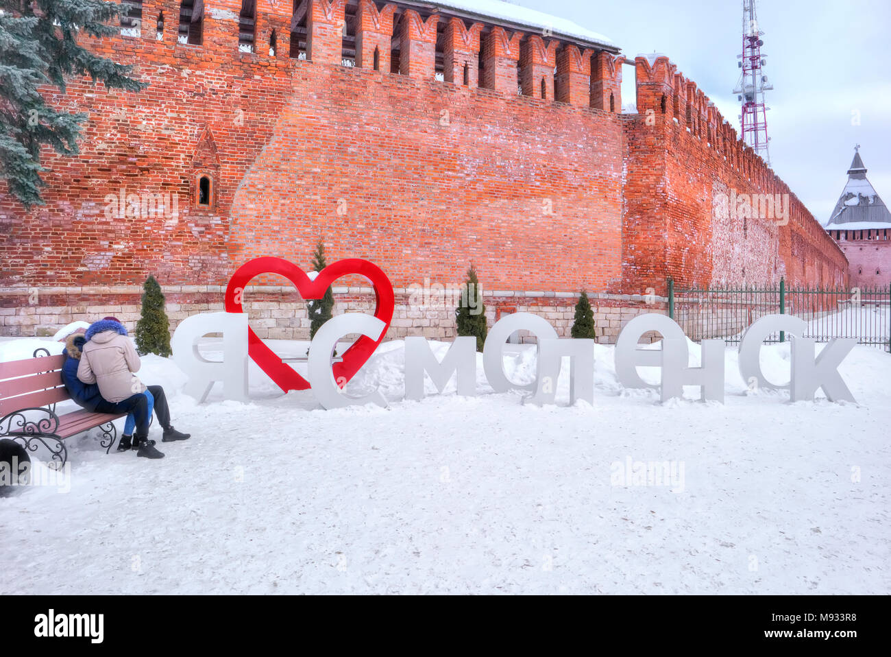 SMOLENSK, RUSSIA - March 08.2018: The guy with the girl on the bench near the installation I love Smolensk on the background of the fortress wall - Stock Image