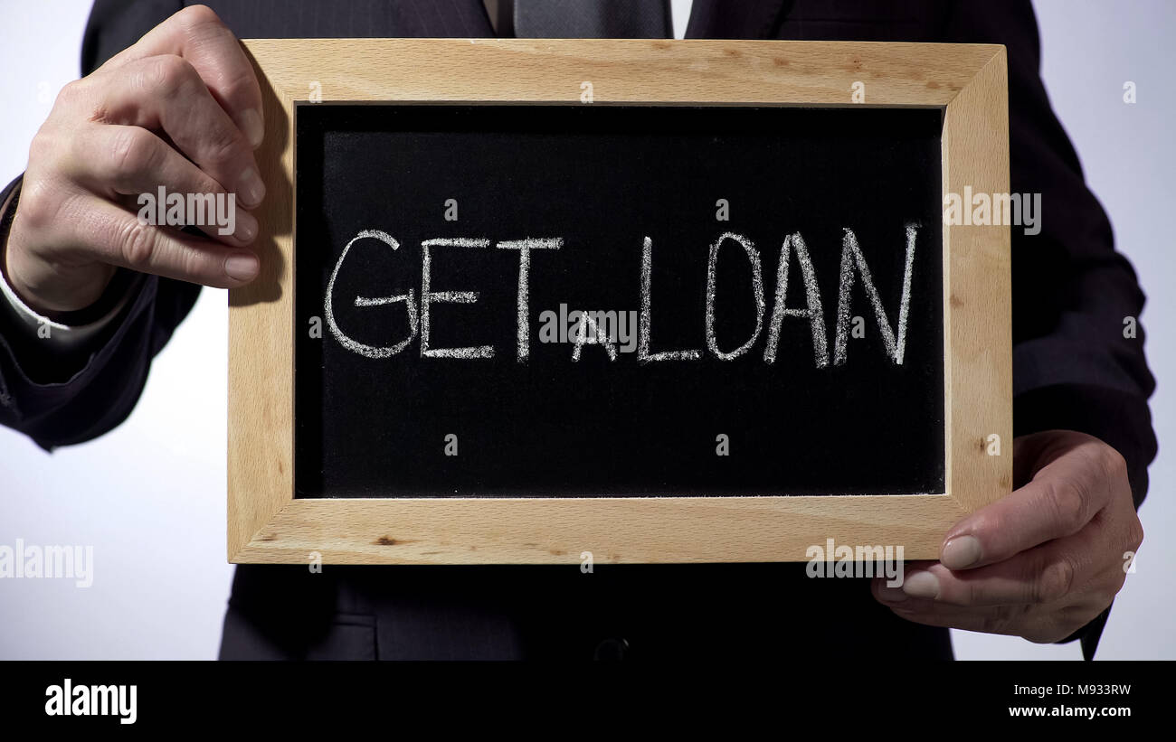 Get a loan written on blackboard, businessman holding sign, business concept - Stock Image