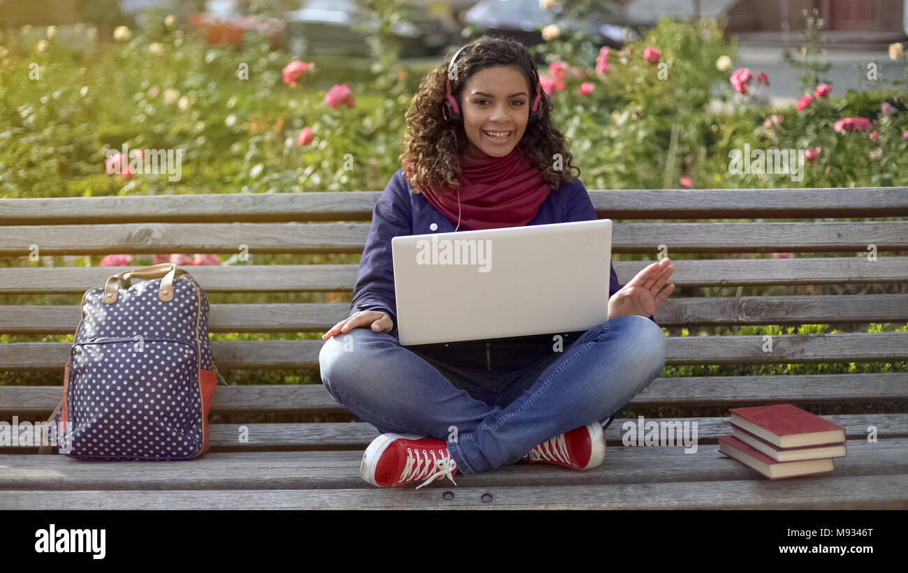 Cute multiracial curly-haired girl in headphones posing for camera and smiling - Stock Image