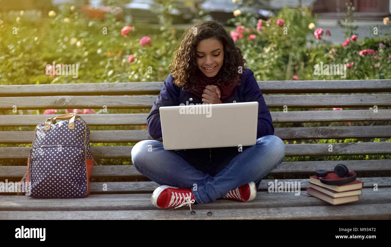 Young wavy-haired woman communicating with friends over laptop camera outdoors - Stock Image
