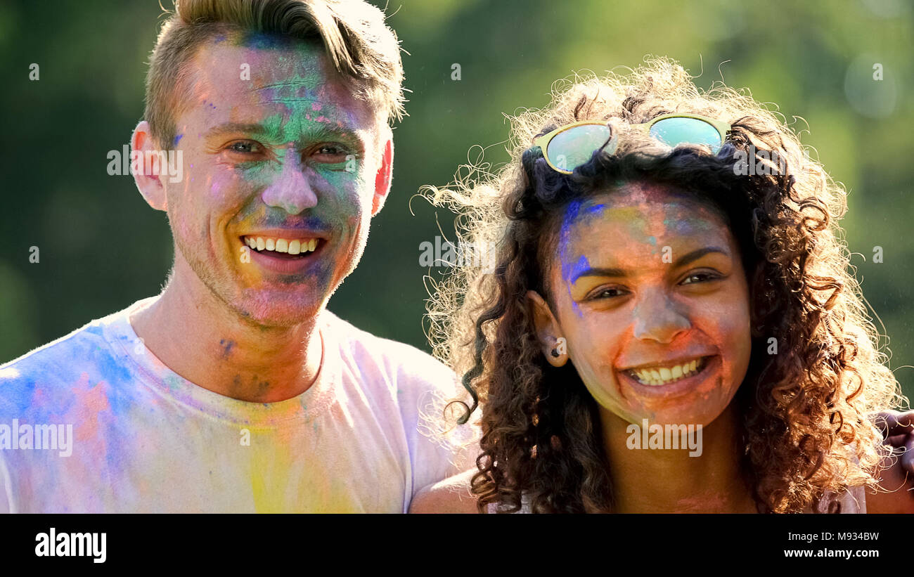 Smiling couple having fun outside on color party celebration, enjoying festival - Stock Image