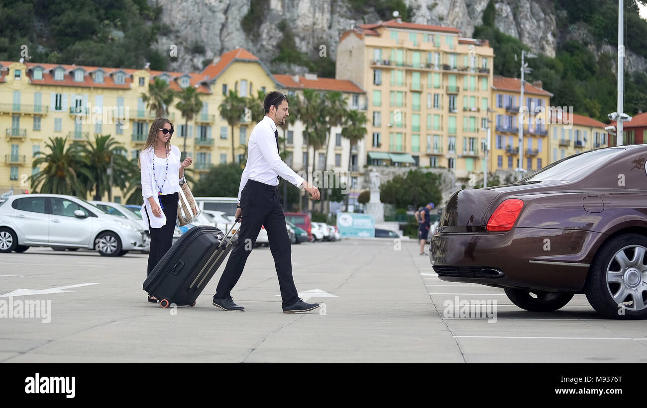 Beautiful businesswoman walking to taxi with chauffer, luxury car services - Stock Image