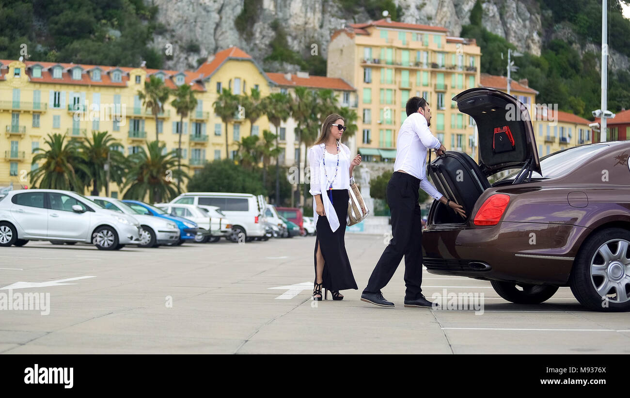 Chauffeur putting luggage in trunk, elite car service for business people - Stock Image