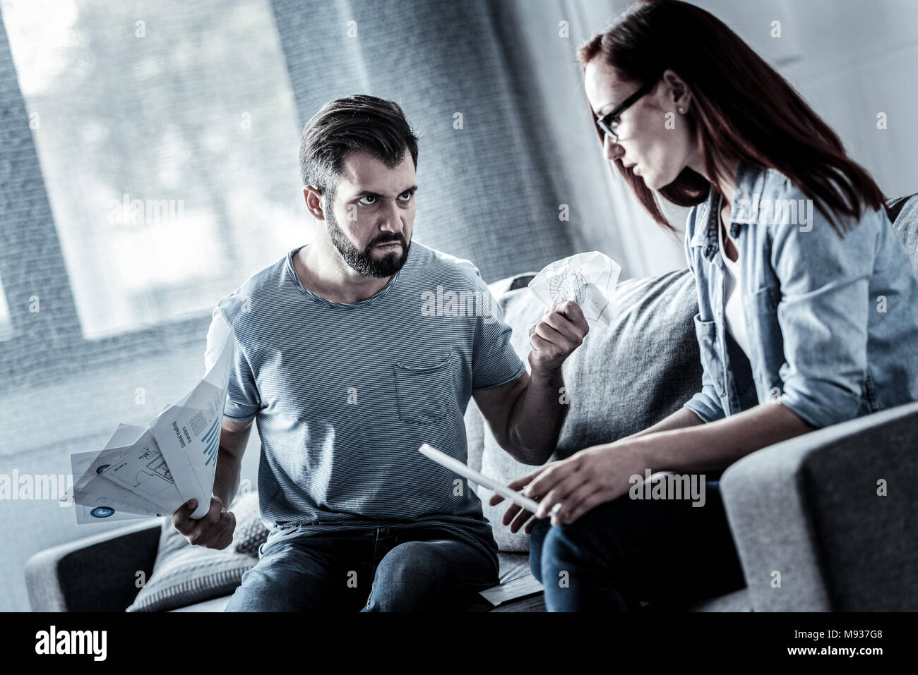 Angry unhappy man holding documents and having bad mood. - Stock Image