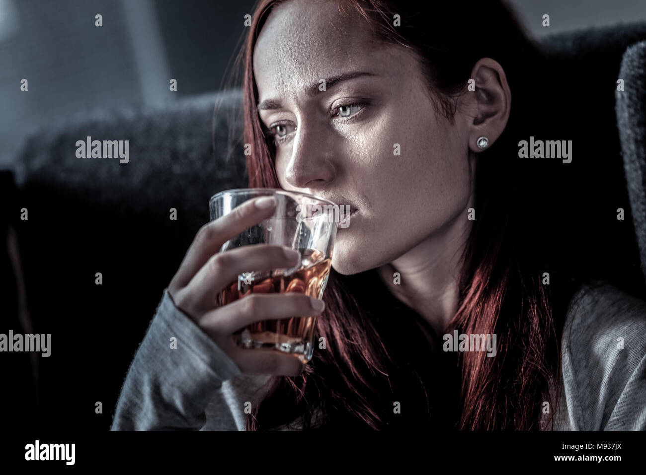 Frustrated unhappy woman looking aside and drinking. - Stock Image