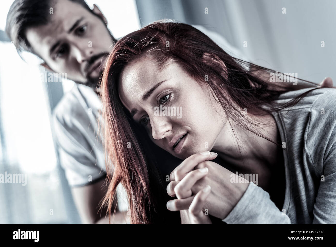 Stressful redhead woman looking down and thinking. - Stock Image