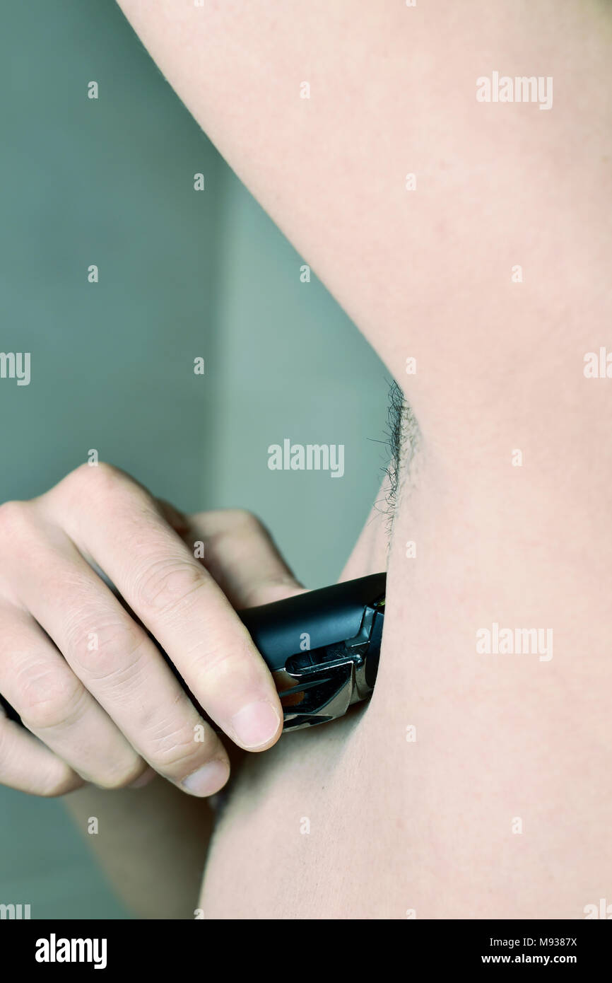 closeup of a young caucasian man in the bathroom trimming the hair of his armpit with an electric trimmer - Stock Image