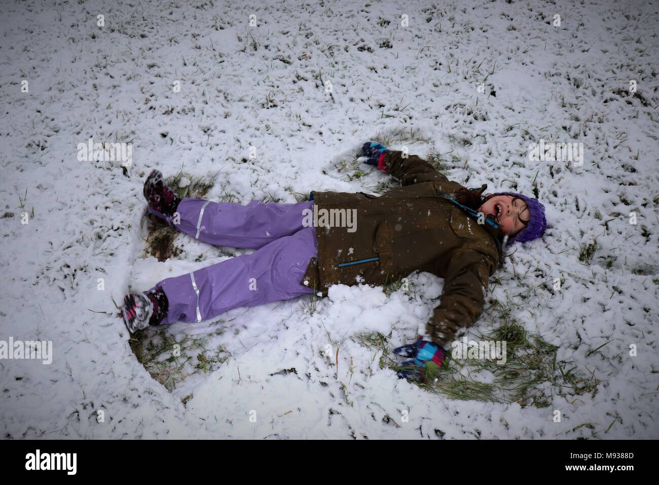 A Red Cheeked Child Making Snow Angels - Stock Image