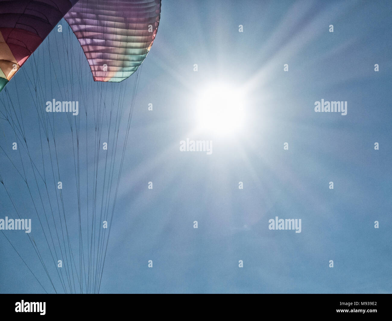 Paragliding: Paraglider with sun and blue sky in background Stock Photo