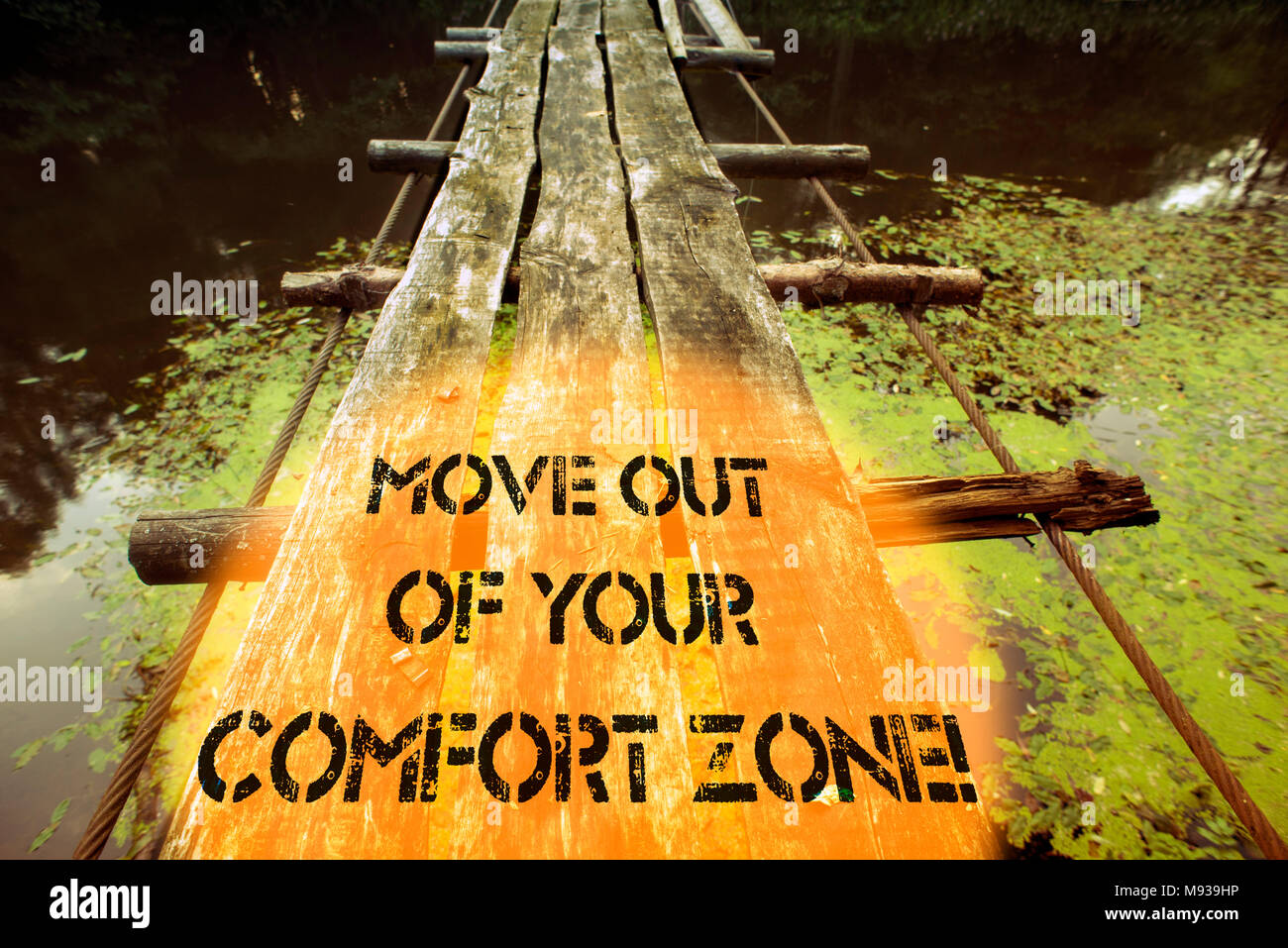 move out of your comfort zone written with ruined wooden bridge fragment over forest river waters Stock Photo