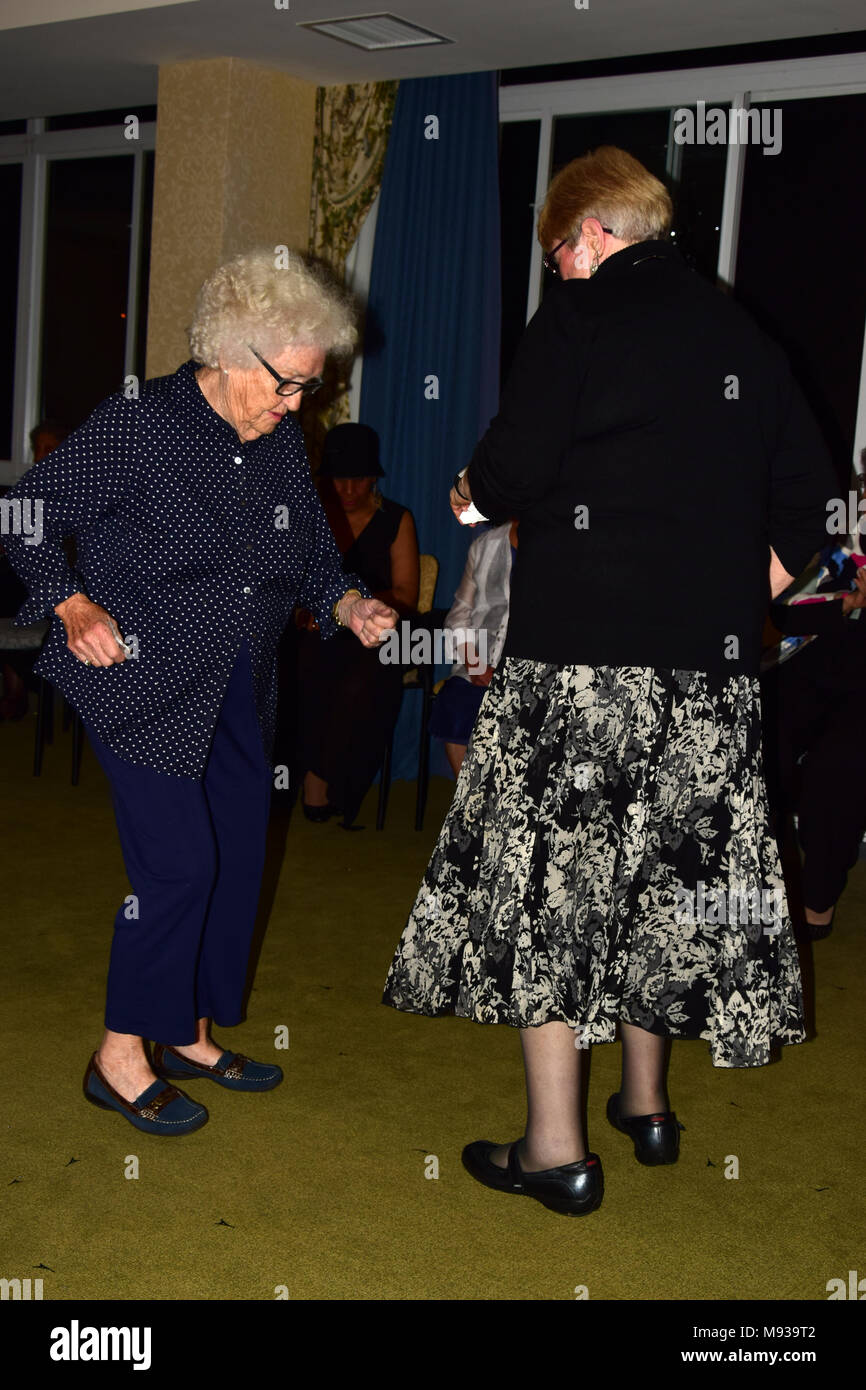 Senior women dancing with younger woman - Stock Image
