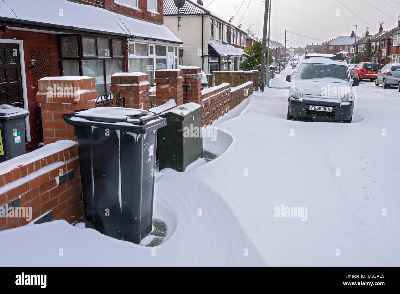 Wheelie bins and small snow drifts in a suburban street, Tameside, Manchester, England, UK - Stock Image