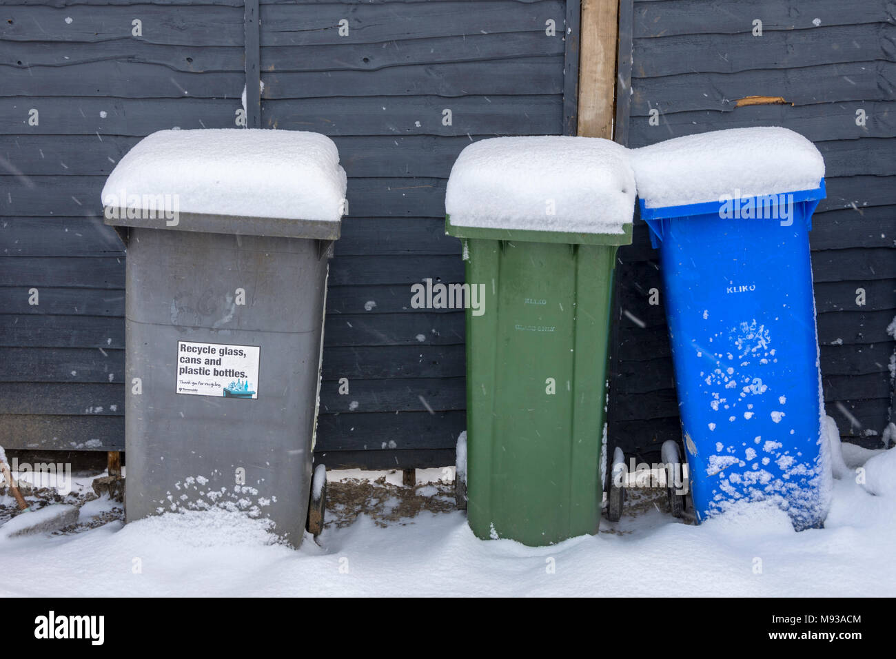 Snow covered wheelie bins in a suburban street, Tameside, Manchester, England, UK - Stock Image