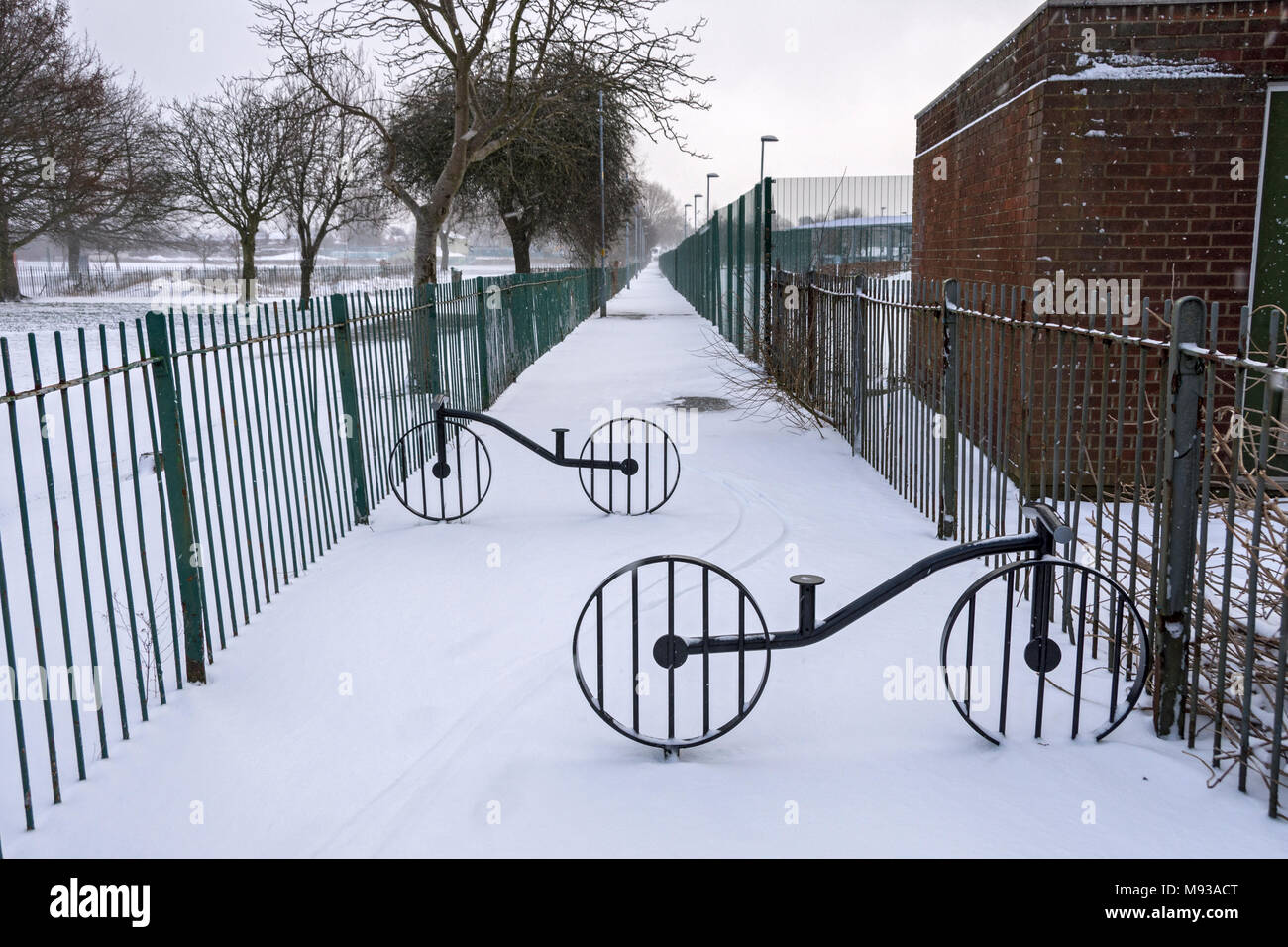 Bicycle styled vehicle barriers on a snow covered footpath, next to Sunnybank Park, Droylsden, Tameside, Manchester, England, UK - Stock Image