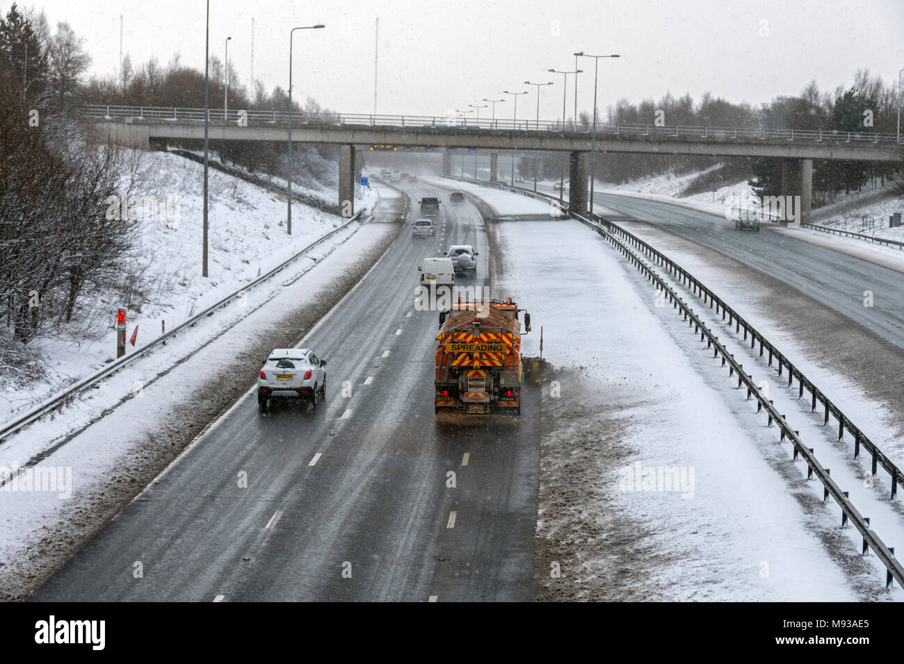 Snow plough and gritting vehicle on the M60 motorway after a snow fall, Ashton-under-Lyne, Tameside, Manchester, England, UK - Stock Image