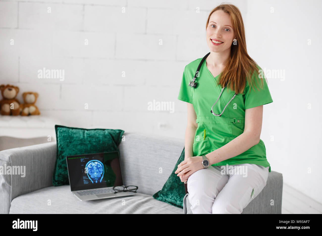 Portrait of friendly doctor neurologist in green uniform. Laptop with tomography images. Children's home doctor concept. - Stock Image