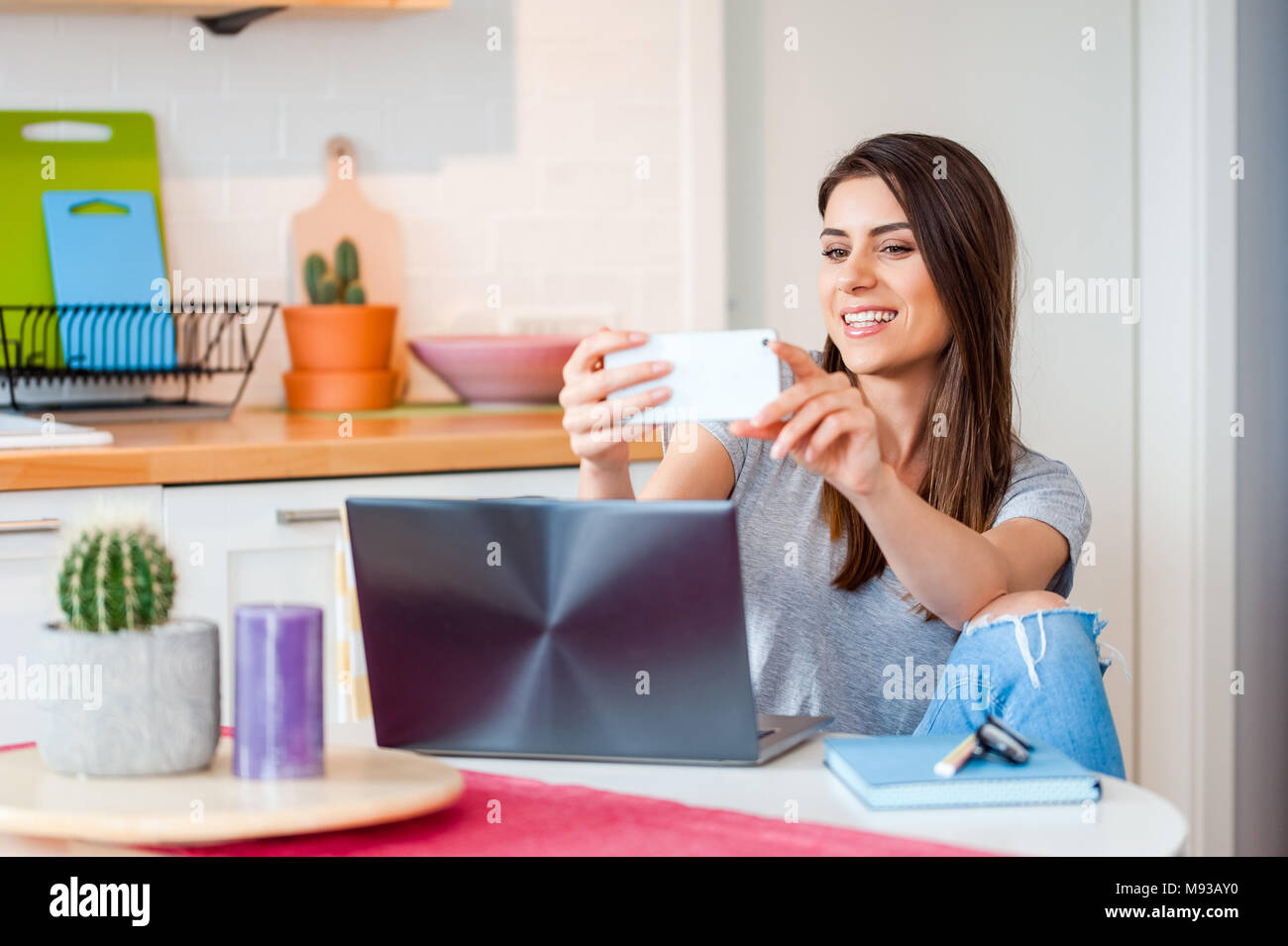 Young woman sitting on chair at table on laptop and taking a selfportrait in a modern decorated home interior. - Stock Image