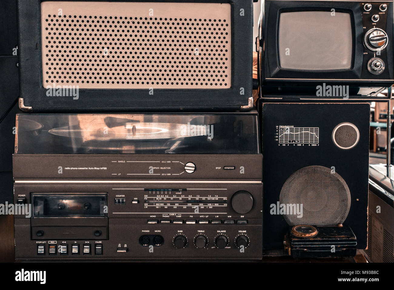 Old vintage audio system with radio, cassette tape recorder, record player, TV set, acoustic speakers - Stock Image