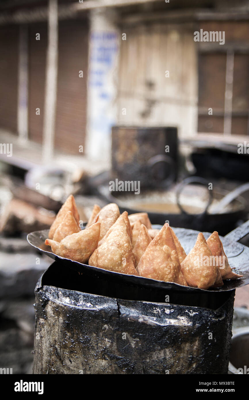 Indian Samosa, deep fried delicious and tasty cheap eats. One of the finest Indian street foods. Stack of triangle shaped pastries, fast food India - Stock Image