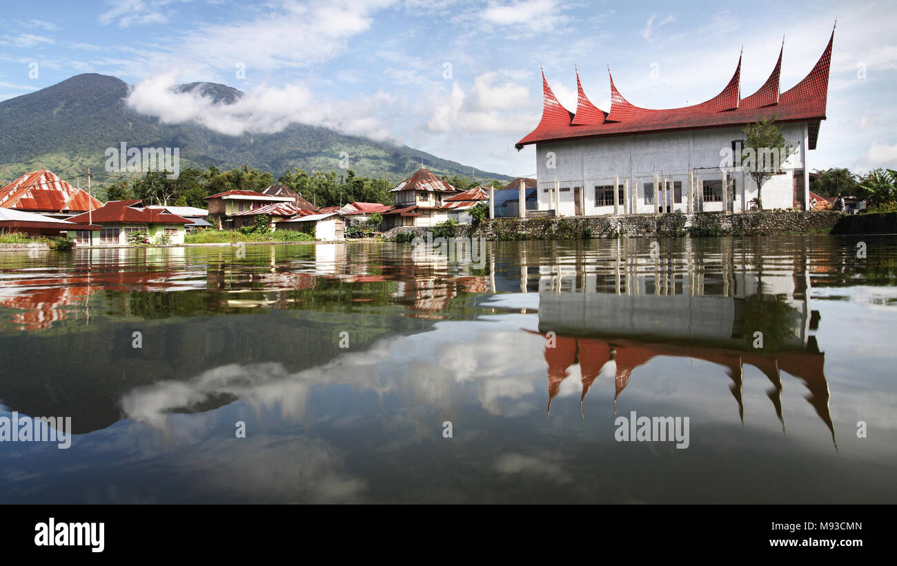 Landscape of Sumatra. Stunning view of Mount Merapi from across a lake with Minangkabau house roof style reflected in water. Symmetrical Mirror Image - Stock Image