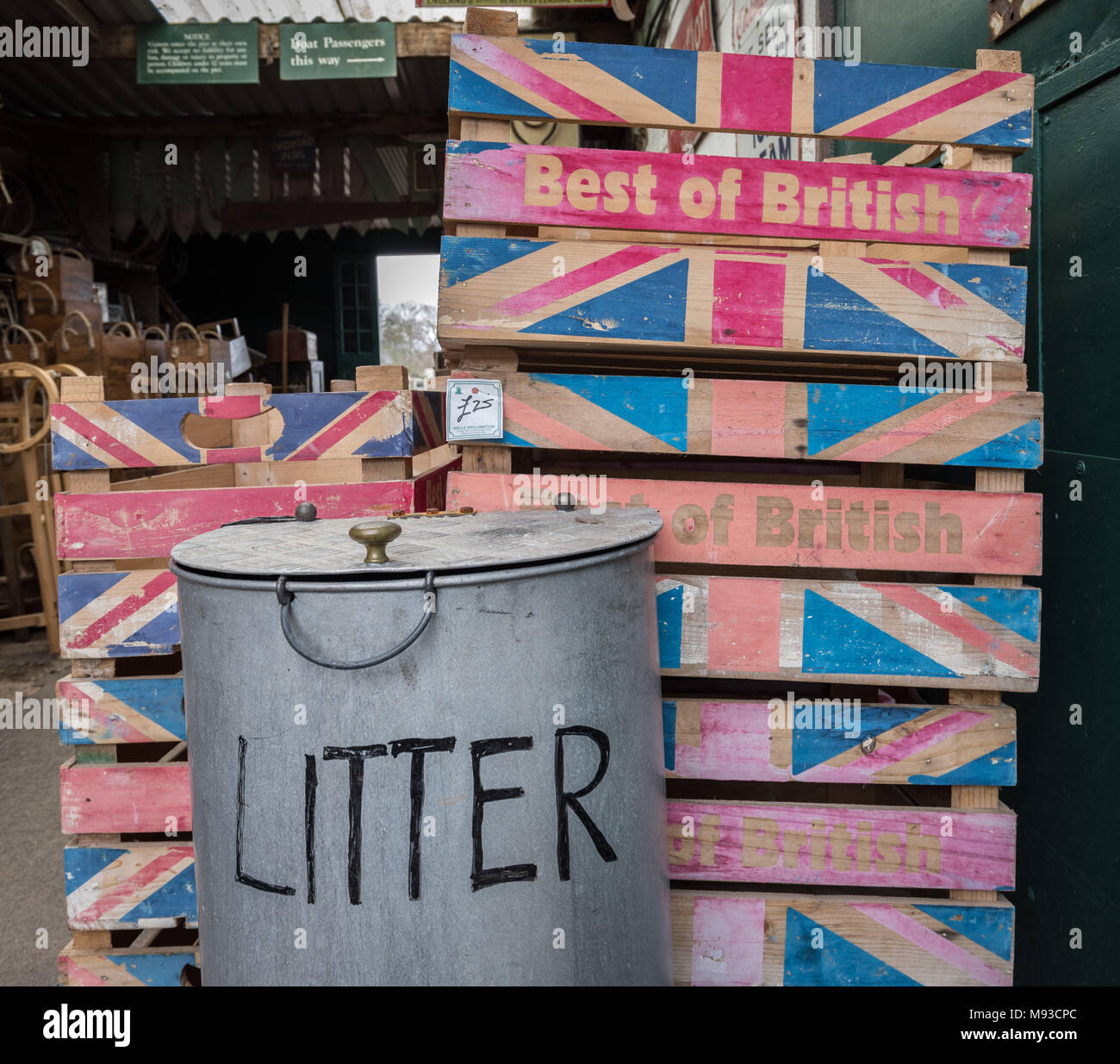 A stack of 'Best of British' wooden vegetable crates stand next to a metallic litter bin. Glastonbury, Somerset. Stock Photo