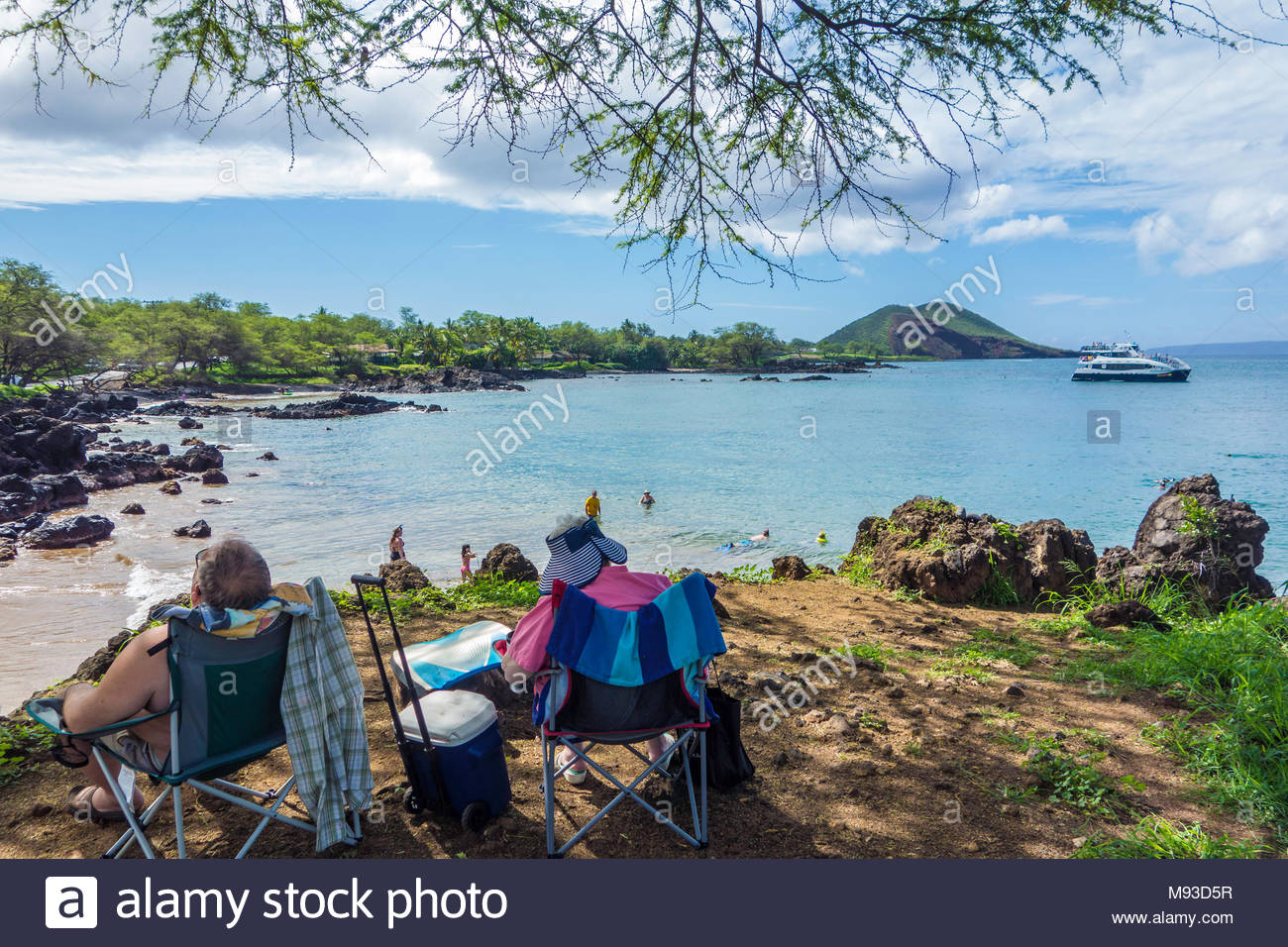 Retired couple relaxing in the shade at Makena Landing Beach Park on the island of Maui in the state of Hawaii USA - Stock Image