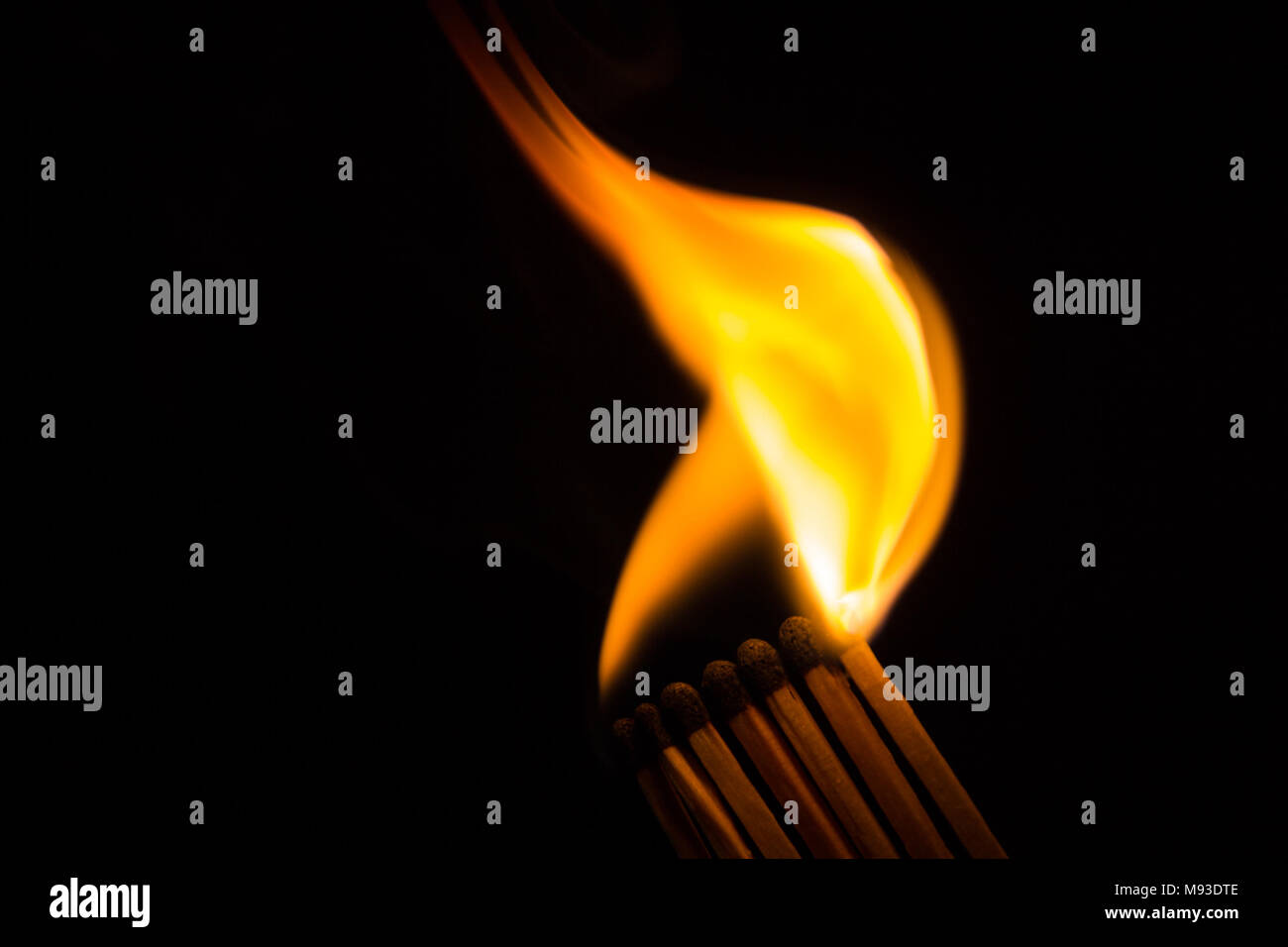 A row of matches is being ignited, spreading the fire - Stock Image