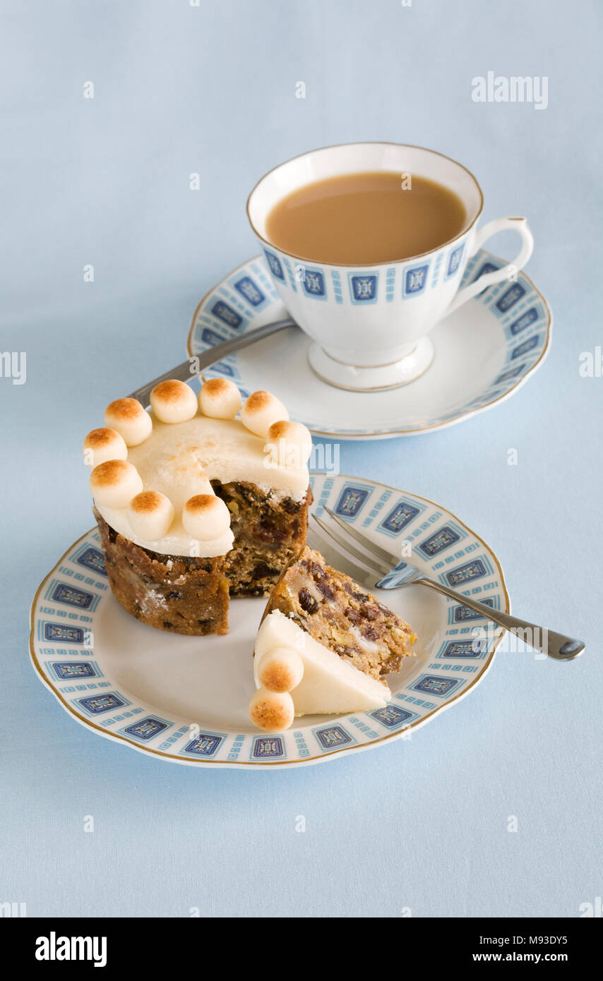 Homebaked miniature Simnel cake and a cup of tea. - Stock Image