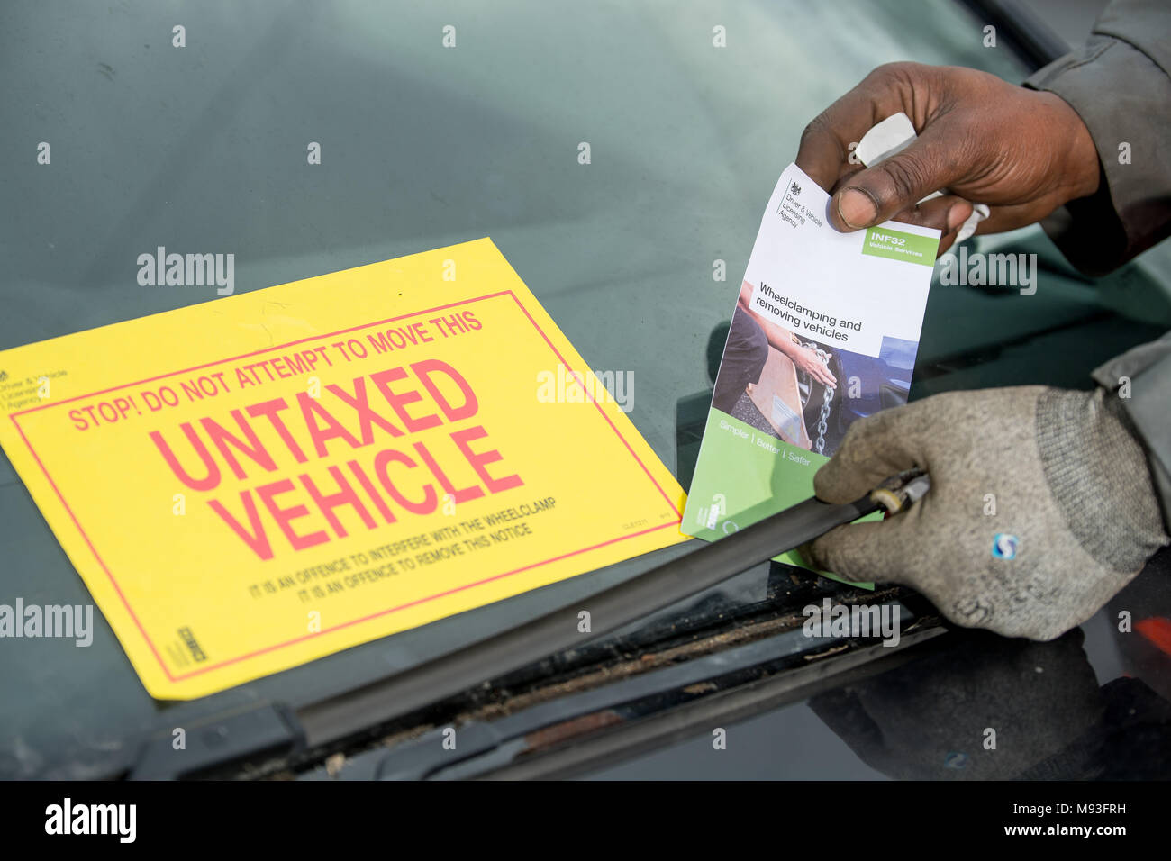 Wheel clamping of untaxed vehicles is becoming more common with the paper tax disc display being abolished and car tax needing to be paid online. - Stock Image