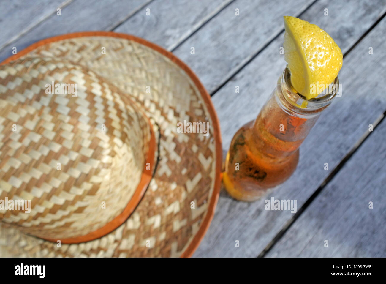 c1c4a00e42b Straw hat with fresh cold beer drink served on a table in a tropical resort.