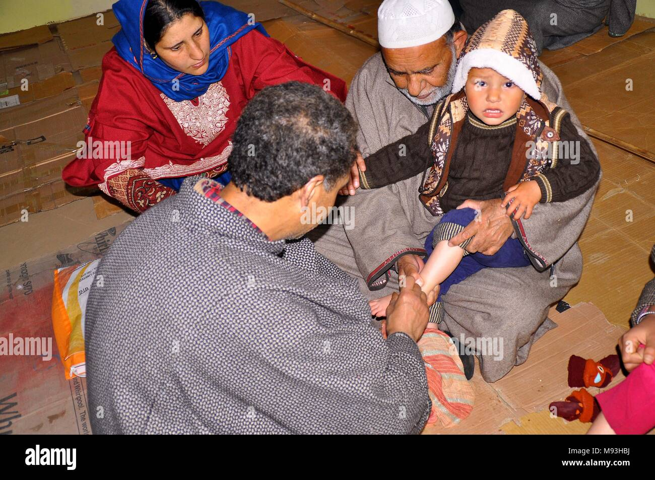 Anantnag, India. 21st Mar, 2018. A Young kashmiri Boy receives leech therapy on 20, March 2018 in Malaknag Anantnag, 48 Kilometer from the the summer capital of Indian administered Kashmir, India. Practitioners of the centuries-old alternative form of treatment use leeches to suck impure blood from the affected patient to treat various ailments. Credit: Muneeb Ul Islam/Pacific Press/Alamy Live News - Stock Image