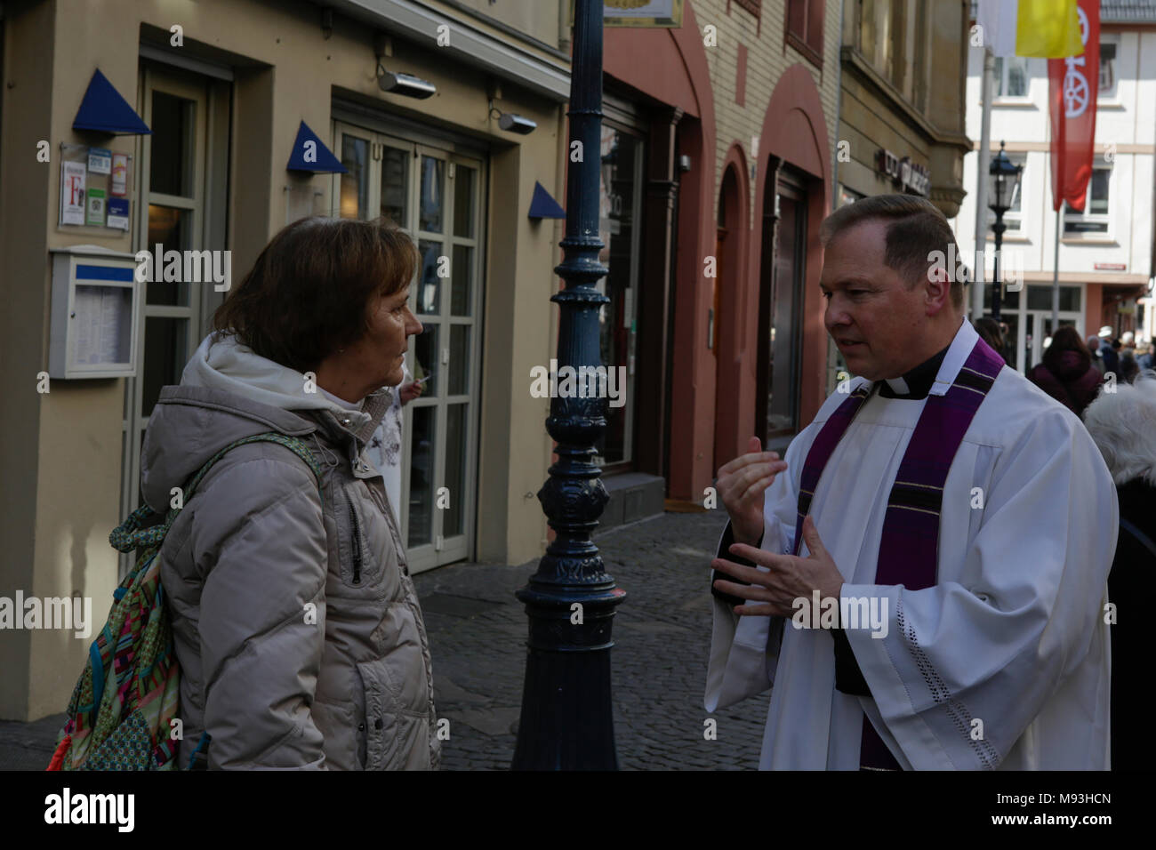A priest talks to a women who stands along the route of the funeral procession for Cardinal Lehmann. The funeral of Cardinal Karl Lehmann was held in the Mainz Cathedral, following a funeral procession from the Augustiner church were he was lying in repose. German President Frank-Walter Steinmeier attended the funeral as representative of the German state. Cardinal Karl Lehmann was the bishop of the Roman Catholic Diocese of Mainz for 33 years until his retirement in 2016. He was also the chairman of the Episcopal Conference of Germany for 21 years until he stepped down from this position in 2 - Stock Image