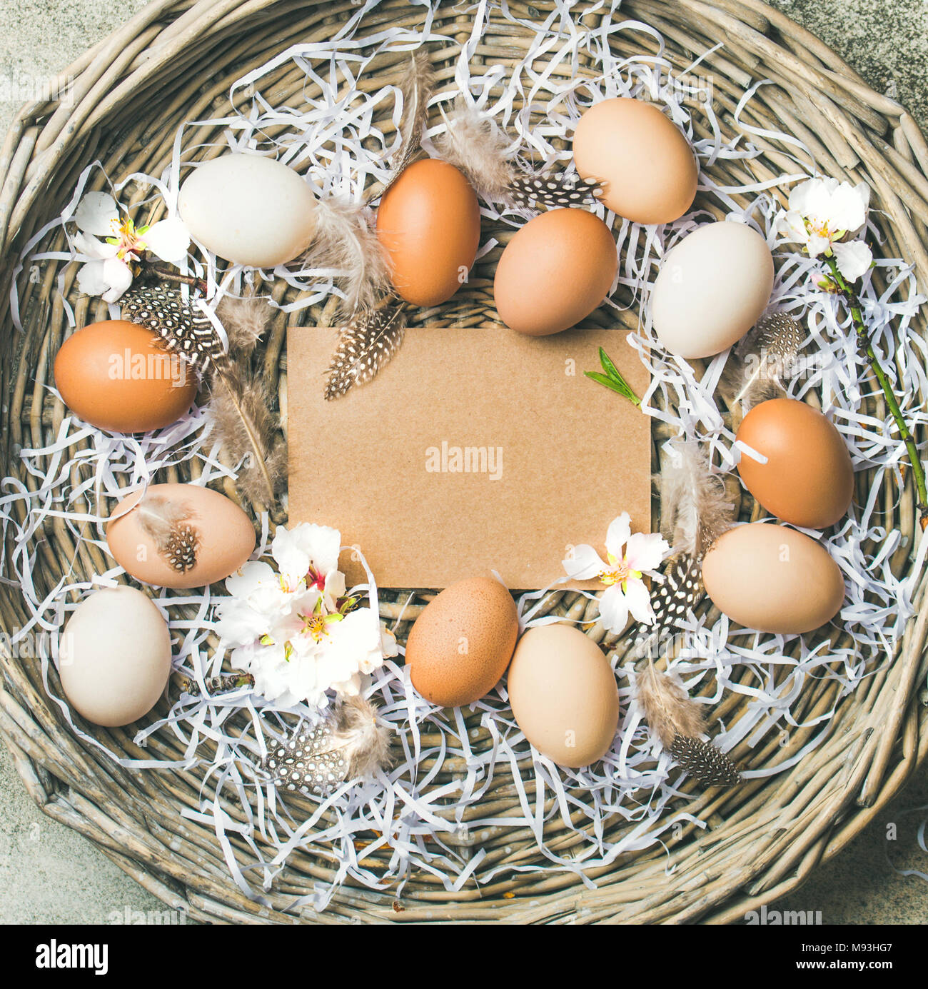 Natural colored eggs for Easter in basket over grey background - Stock Image