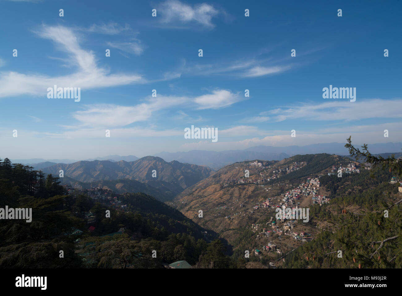 Scenic beautiful mountain landscape valley and town nature with blue sky and clouds in Shimla to Kalka in Himachal Pradesh, North India, India, Asia - Stock Image