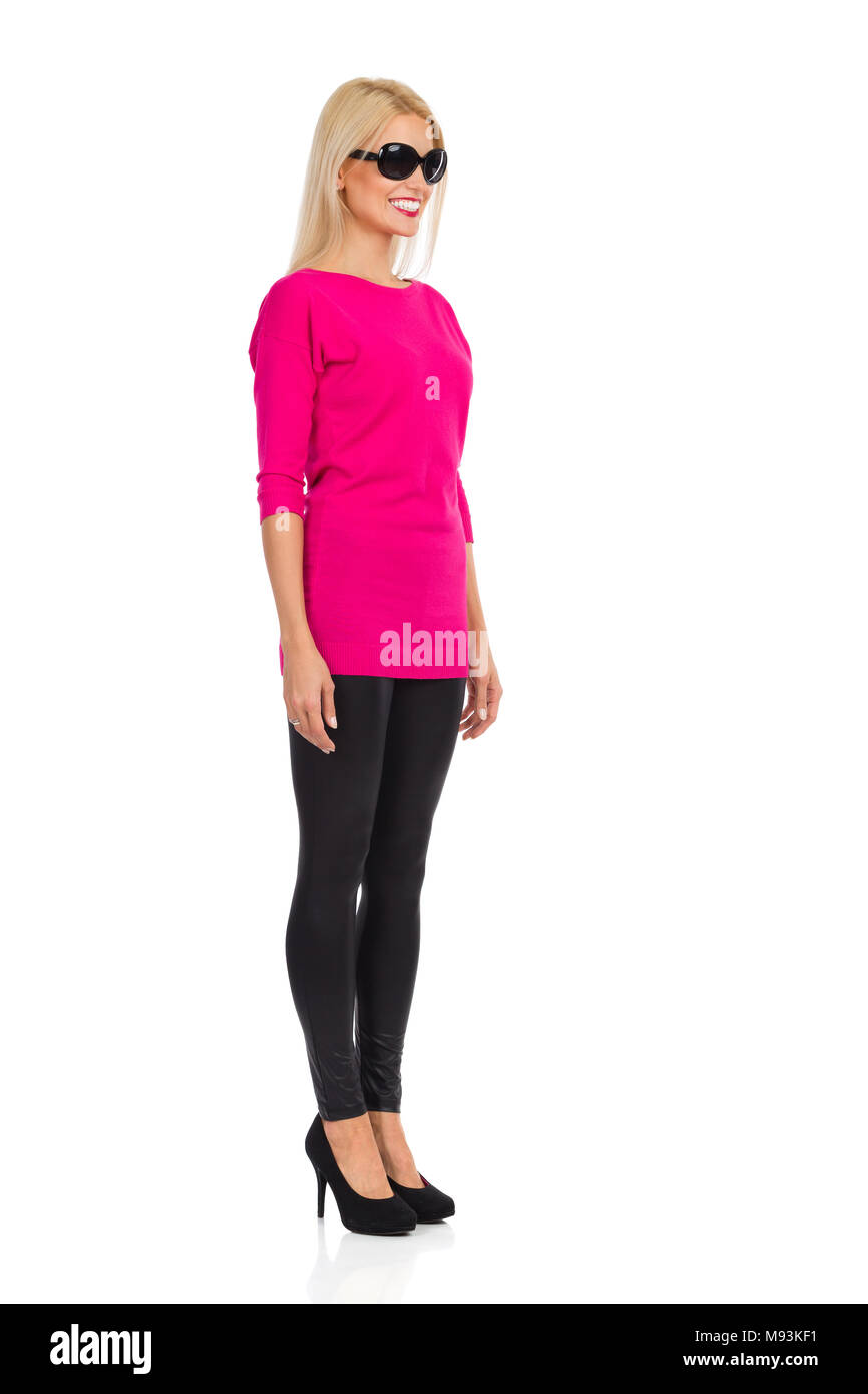 Smiling beautiful blond woman in sunglasses, black leggings, high heels and pink sweater is standing at attention and looking away. Front side view. F - Stock Image