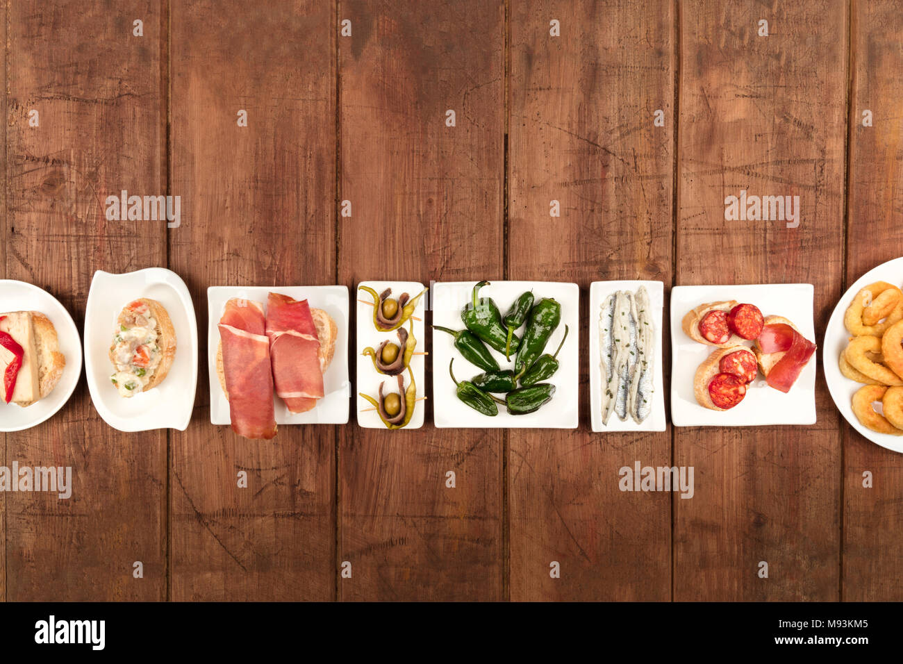 An overhead photo of an assortment of Spanish tapas food, shot from the top on a dark rustic background with a place for text - Stock Image