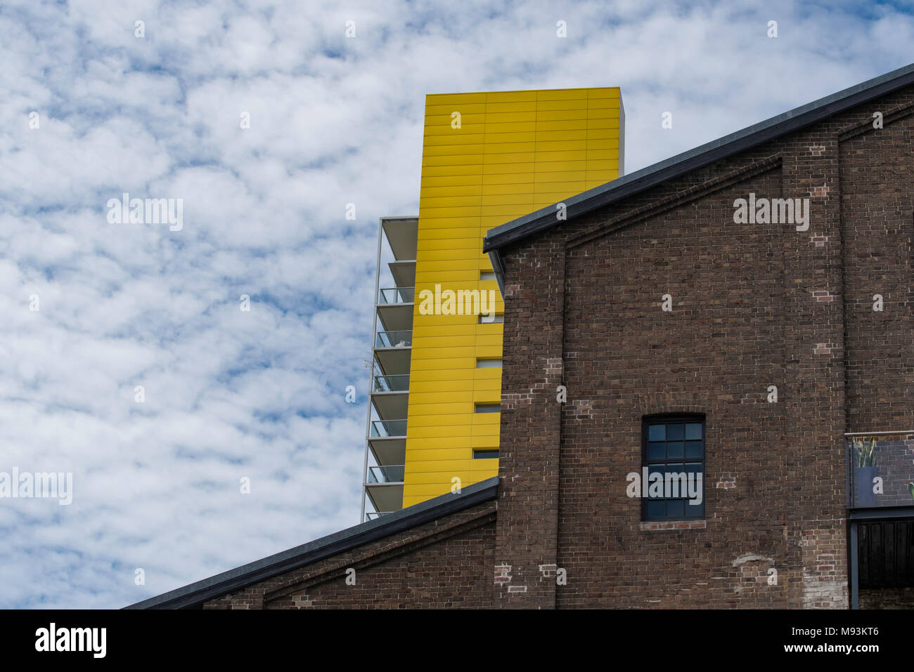 An old brick built warehouse in Pyrmont NSW with a brightly coloured modern apartment  in the background. - Stock Image