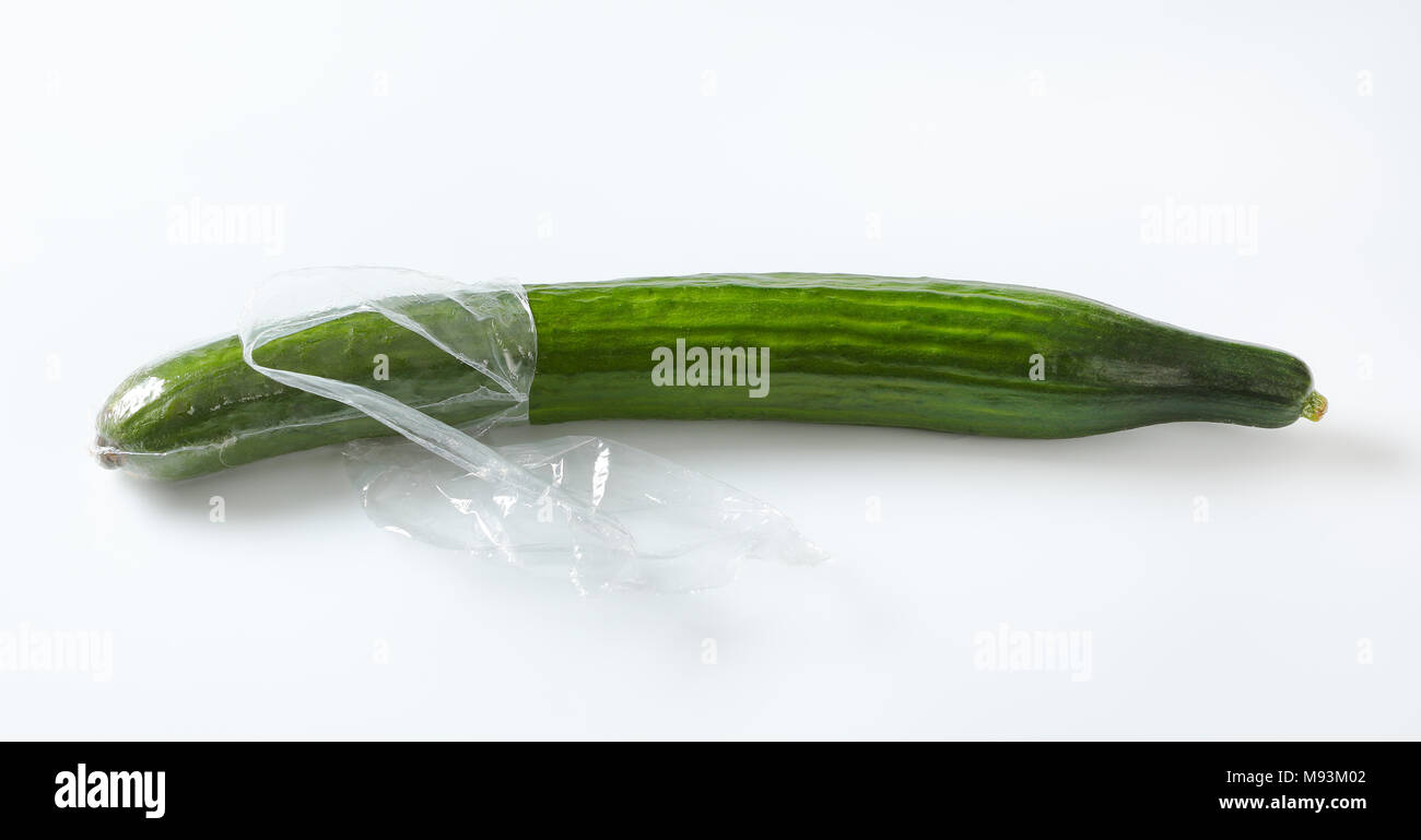single long cucumber unwrapped and unpeeled on white background - Stock Image