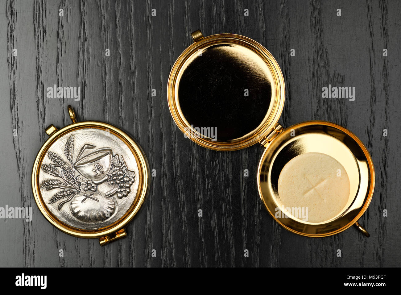 Host wafer of bread to be consecrated as the Body of Christ at Mass in a gold Pyx on a black oak table - Stock Image