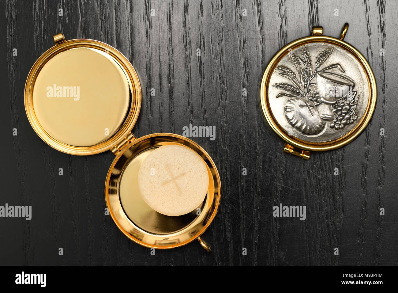 Host wafer of bread to be consecrated as the Body of Christ at a Roman Catholic Mass in a gold Pyx on a black oak table - Stock Image