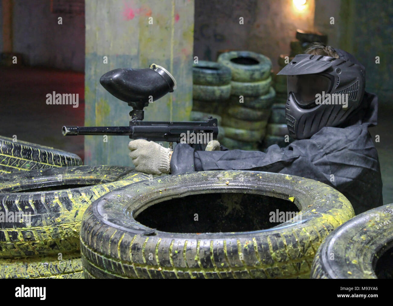 A man with a marker for paintball in the woods sitting for tires in the ambush. Stock Photo